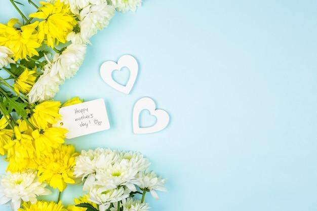 Etiqueta con palabras felices del día de la madre cerca de corazones y racimos de flores frescas