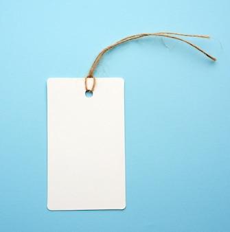 Etiqueta de papel blanco en blanco con cuerda blanca sobre azul