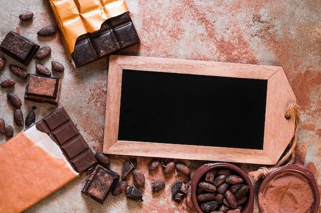 Etiqueta de pizarra en blanco con barra de chocolate, granos de cacao y polvo en la mesa