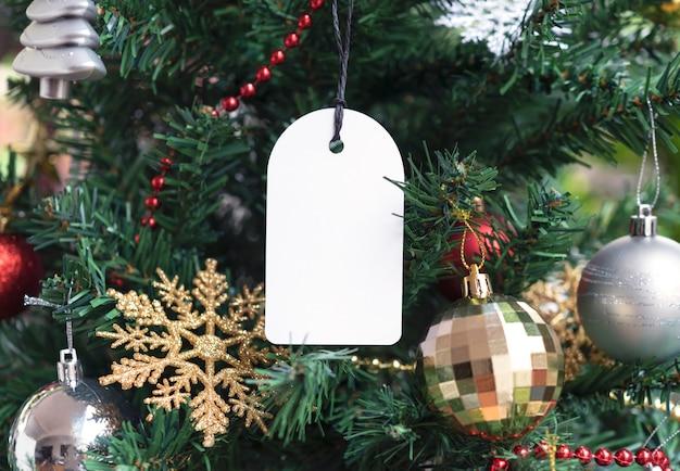 Etiqueta de regalo hecha de tarjeta reciclada en el fondo del árbol de navidad. promoción venta para navidad y feliz año nuevo.