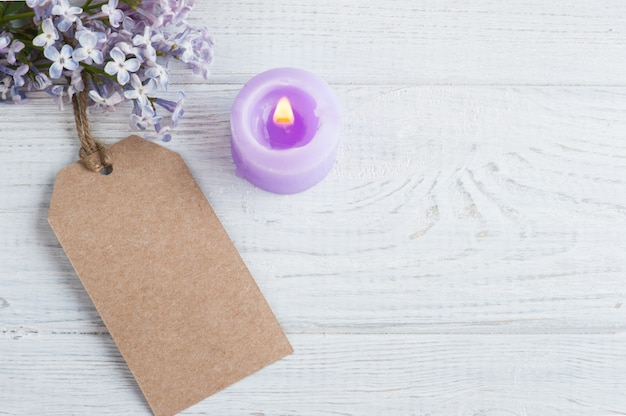 Etiqueta de regalo kraft, velas encendidas y flores de color lila