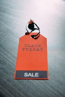 Etiqueta roja con inscripción sobre fondo de madera oscura con un diseño elegante, primer plano. concepto de viernes negro.