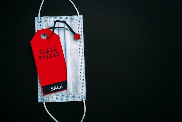Etiqueta roja con la inscripción viernes negro en el fondo de la máscara médica, concepto de compra segura.