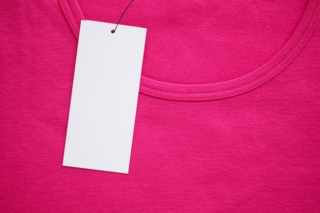 Etiqueta de ropa blanca en blanco en la nueva camisa rosa