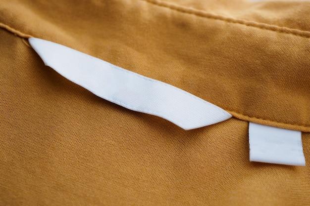Etiqueta de ropa en blanco blanco sobre fondo de camisa marrón
