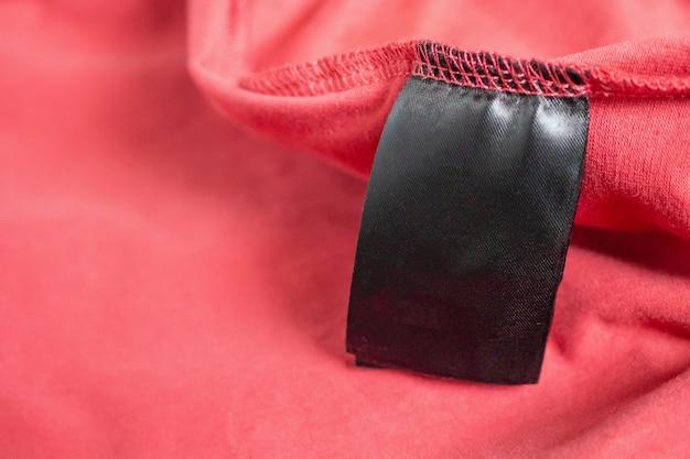 Etiqueta de ropa de color negro en blanco en camiseta roja