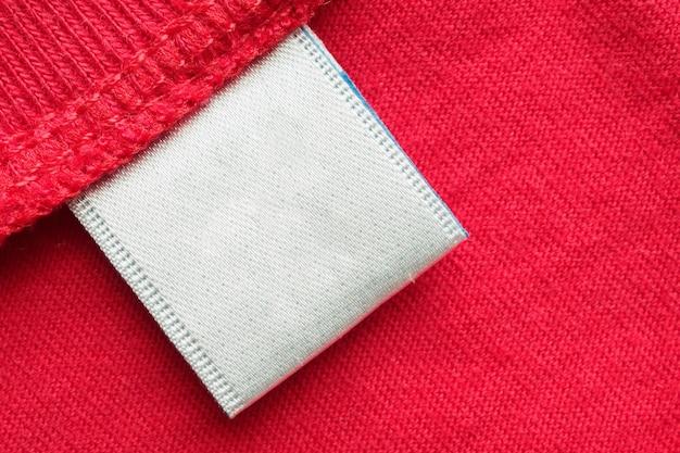Etiqueta de ropa de cuidado de lavandería en blanco blanco sobre fondo de camisa de algodón rojo