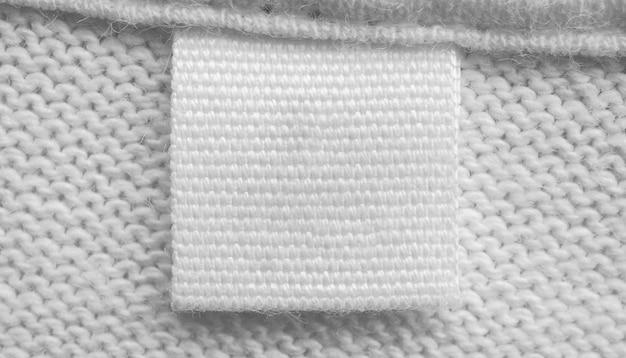 Etiqueta de ropa de cuidado de lavandería en blanco blanco sobre fondo de camisa de algodón