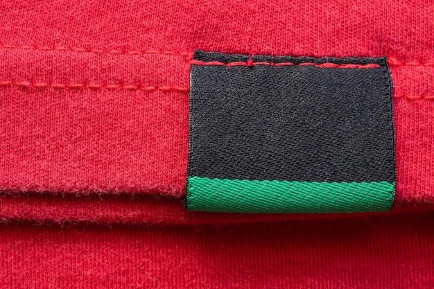 Etiqueta de ropa de cuidado de lavandería en blanco negro sobre fondo de camisa de algodón rojo