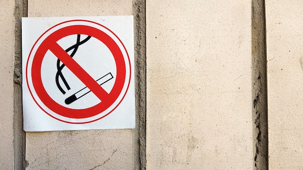 Etiqueta de señal redonda de no fumar en la ciudad. señales de no fumar que rastrean las paredes de todas las áreas para limitar el área de fumadores. cartel rojo y negro con un fondo de piedra gris texturizado - no fumar.