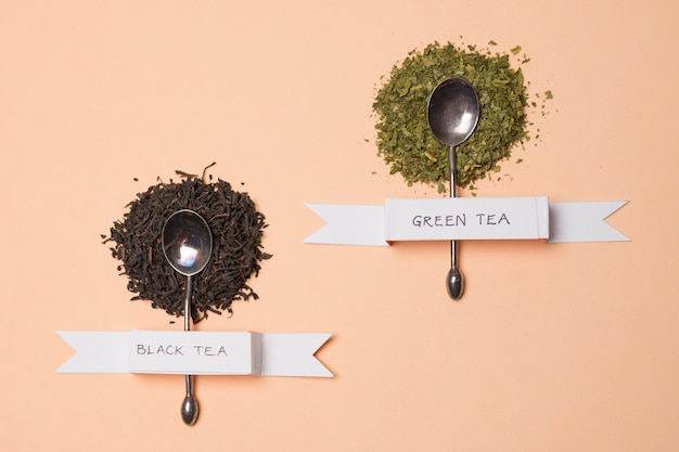 Etiqueta de té de hierbas negro y verde en las hierbas sobre el telón de fondo de melocotón
