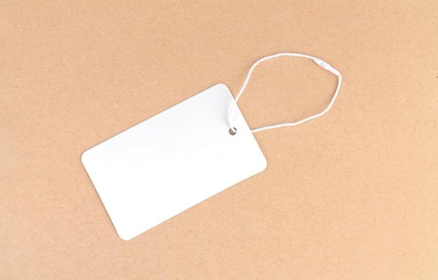 Una etiqueta de tela en blanco o etiqueta de precio sobre fondo marrón