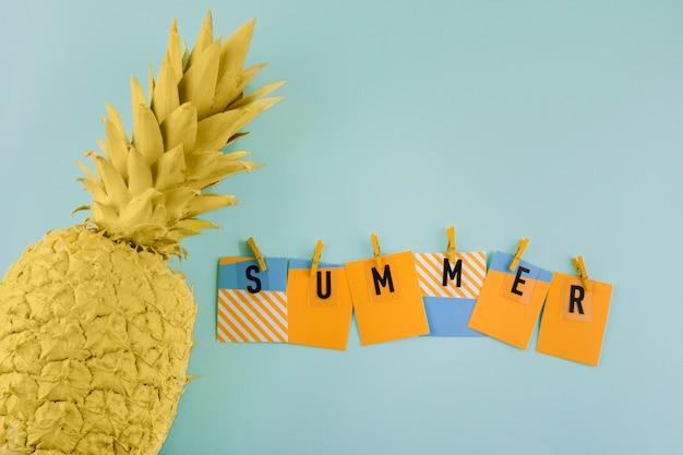 Etiqueta de verano con pinza para la ropa cerca de la piña amarilla pintada sobre fondo azul