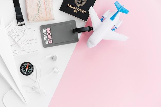 Etiqueta de viajero mundial con pasaporte; mapa; brújula; entradas; avión de juguete y auricular sobre fondo blanco y rosa