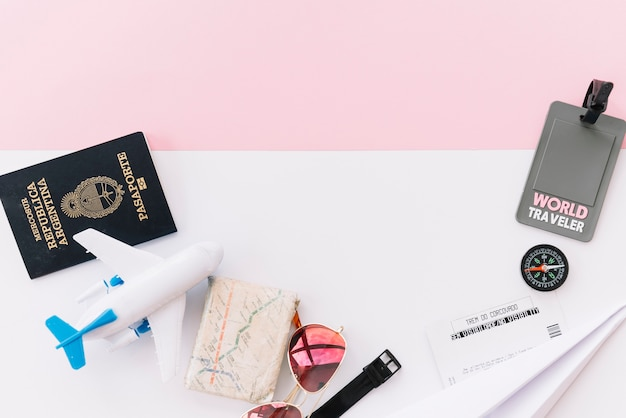 Etiqueta de viajero del mundo gris con pasaporte; mapa; brújula; entradas; avión de juguete; gafas de sol y reloj de pulsera en doble fondo.