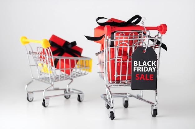 Etiqueta de viernes negro con caja de regalo roja en carrito de compras