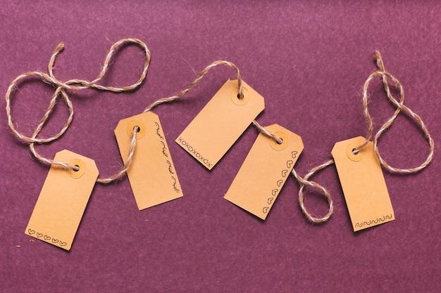 Etiquetas atadas con fondo morado
