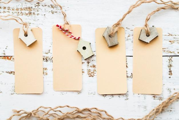 Etiquetas en blanco atadas con pajarera en miniatura en el escritorio blanco