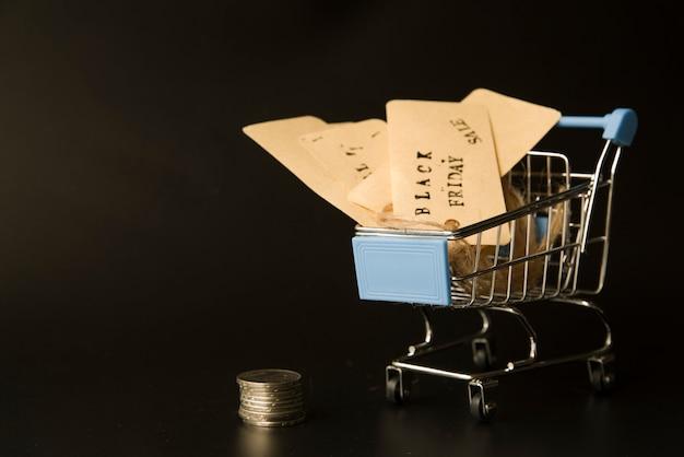 Etiquetas en carro de compras cerca de monedas
