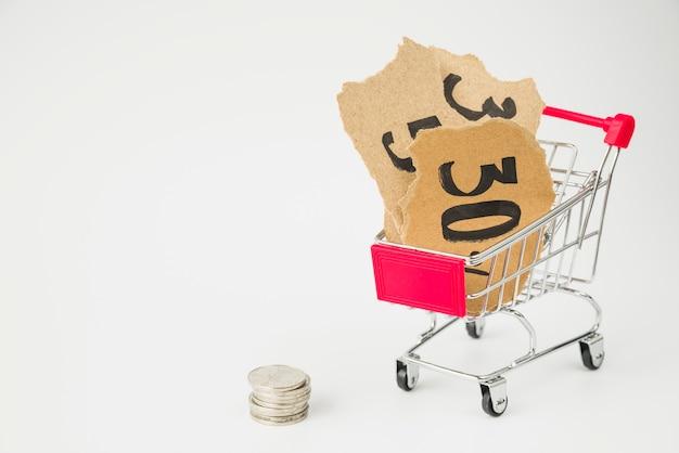 Etiquetas de cartón en el carrito de compras cerca de las monedas