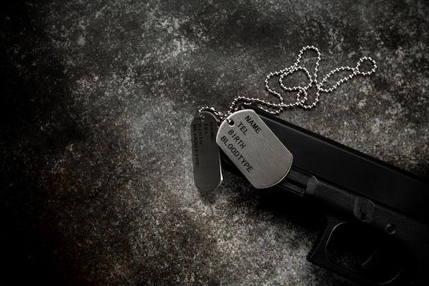Etiquetas de perro militares en blanco y un arma en la placa de metal oxidada abandonada. - concepto de recuerdos y sacrificios.