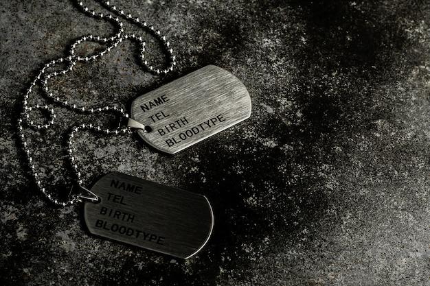 Etiquetas de perro militares en blanco en la placa de metal oxidada abandonada.