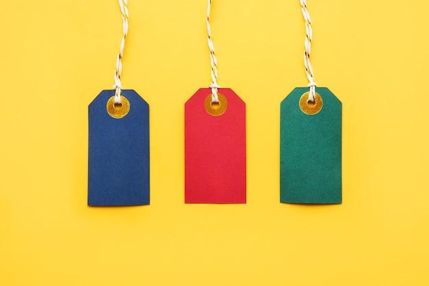 Etiquetas de venta en blanco de colores sobre un fondo amarillo brillante. viernes negro y concepto de ventas. vista superior, espacio de copia