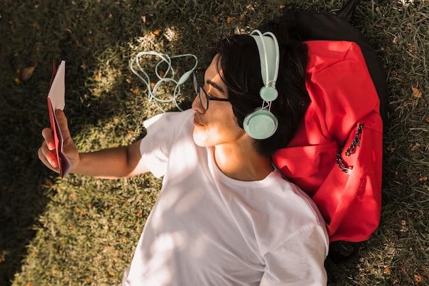 Étnico adolescente tendido en el suelo con el libro