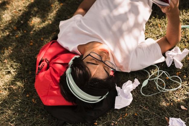 Étnico adolescente tendido en el suelo