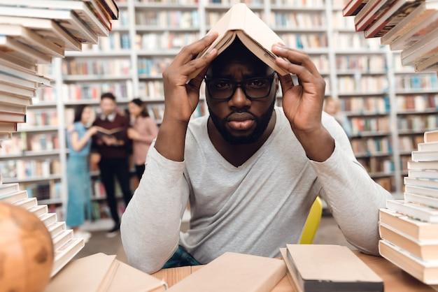 Étnico afroamericano rodeado de libros en la biblioteca