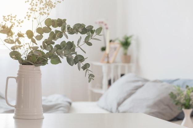 Eucalipto y gypsophila en jarra en dormitorio blanco