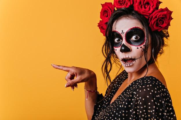 """à ¢ â € â """"retrato perdido de niña sorprendida que señala con el dedo a la izquierda. mujer sorprendida en imagen de halloween posando en pared aislada"""