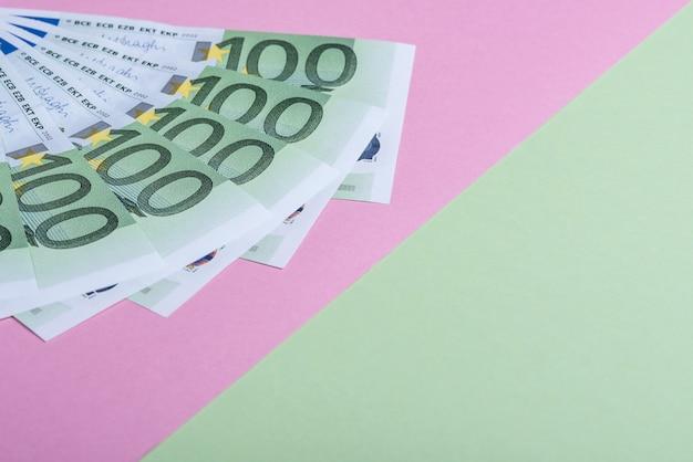 Euro en efectivo sobre un fondo rosa y verde