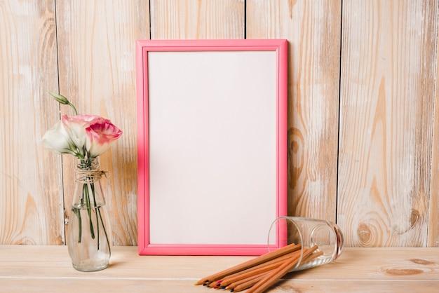 Eustoma en florero de vidrio; lápices de colores y marco de fotos blanco con borde rosa en mesa de madera