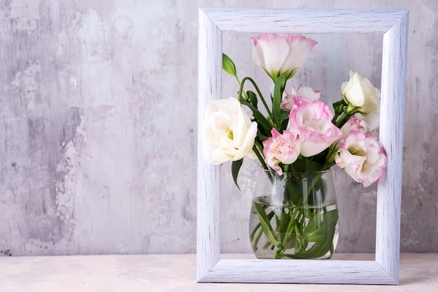 Eustoma flores en florero en marco de fotos en la mesa cerca de la pared de piedra, espacio para texto.