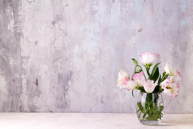 Eustoma flores en florero sobre la mesa cerca de la pared de piedra, espacio para texto. en blanco para postales