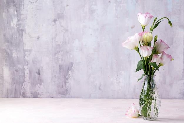 Eustoma flores en florero sobre la mesa cerca de la pared de piedra, espacio para texto.