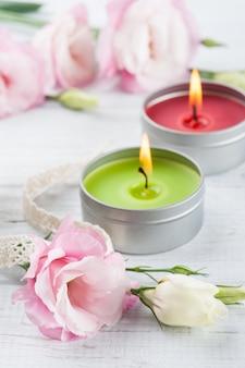 Eustomas rosa sobre una tabla de madera blanca, velas encendidas