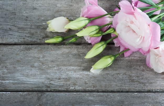 Eustomas rosa sobre tabla de madera vieja