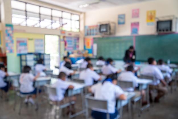 Evaluación de la educación, imagen borrosa de la prueba de escritura en el examen con el grupo de estudiantes asiáticos detrás del niño concentrado en la escuela primaria