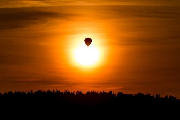 Evento deportivo en el cielo. vuelo en globo sobre el bosque al atardecer. noche romántica colorida tranquila con luz del sol en la naturaleza. cerrar vista de globo en el horizonte.