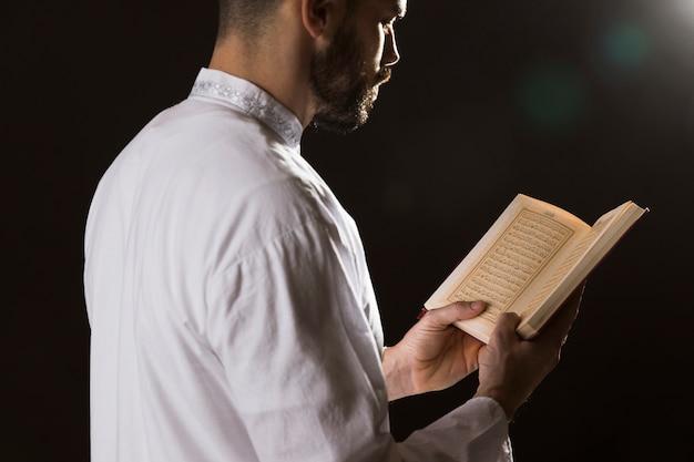 Evento de ramadam y hombre árabe leyendo del corán