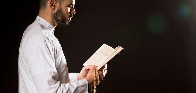 Evento de ramadam y hombre árabe de pie de lado y leer