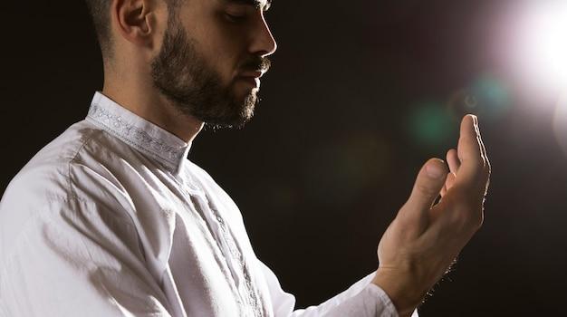 Evento de ramadam y hombre árabe rezando tiro medio