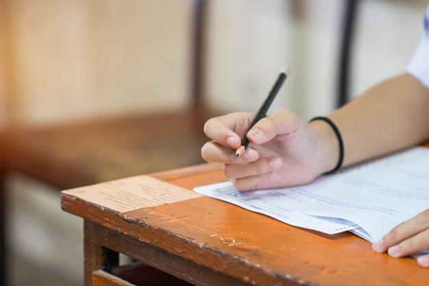 Examen de escritura del alumno en una hoja de respuestas en papel