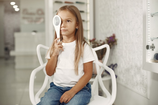 Examen y examen de la vista para niños. niña con chequeo ocular, con foróptero. examen de la vista para niños