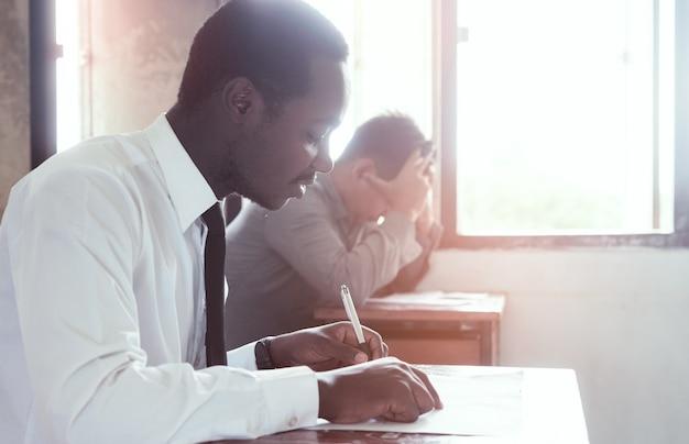 Examen con hombre africano haciendo prueba educativa con estrés en el aula.