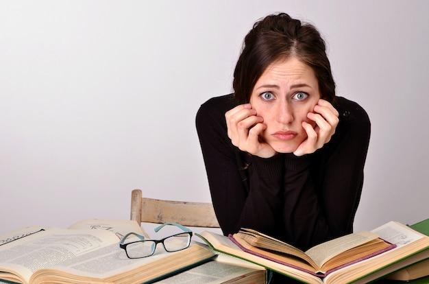 Examen de libros de niña dificultades de suéter negro enseña en la mesa cansado alegra emociones