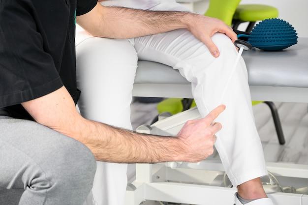 Examen neurológico el neurólogo prueba los reflejos en una paciente con un martillo