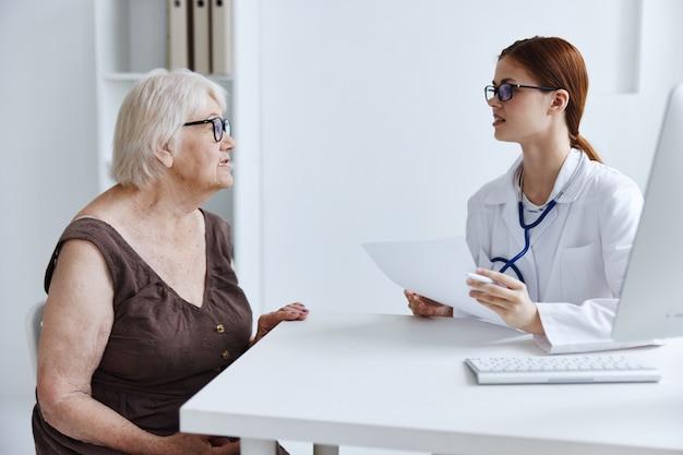 Examen de paciente anciana por un médico de atención médica